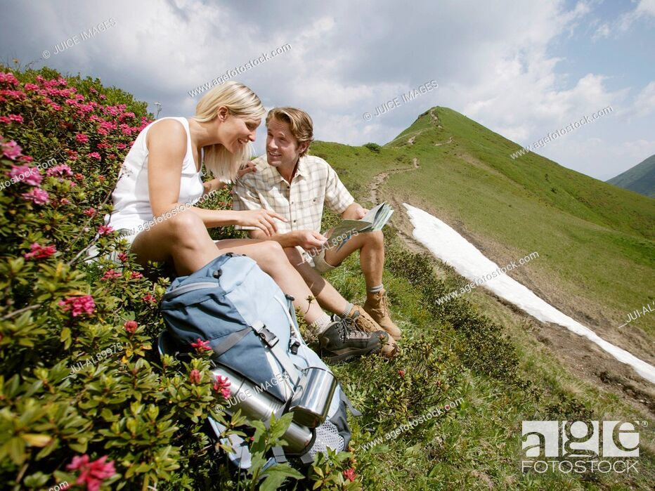 Stock Photo: Couple sitting on mountain side, Kleinwalsertal, Allgau, Germany.