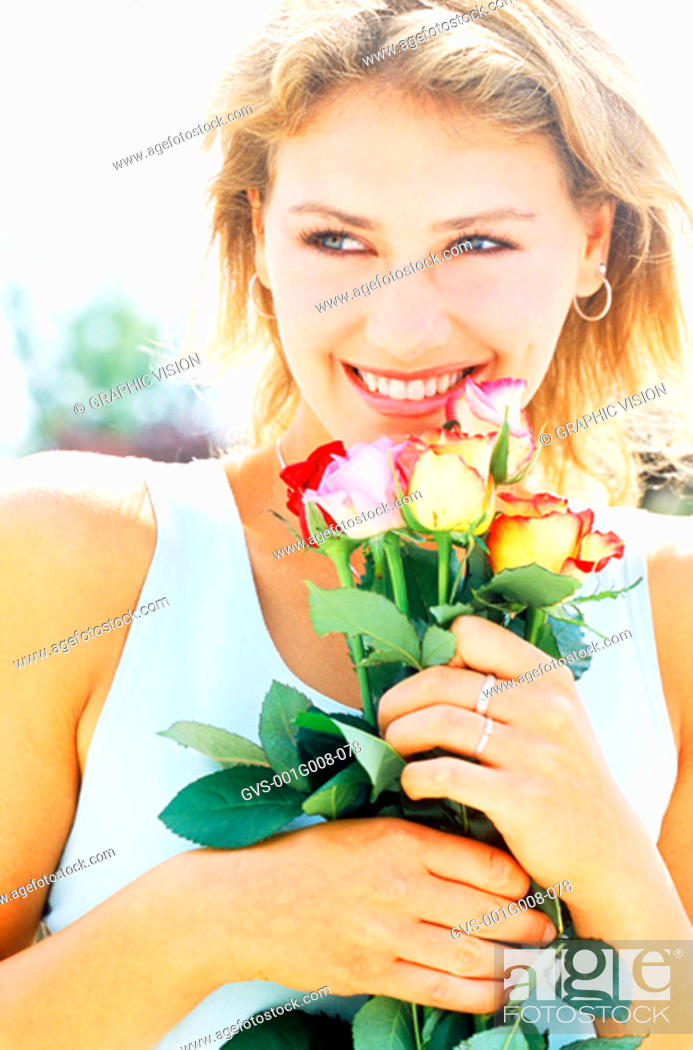 Stock Photo: Portrait of a young woman holding flowers.