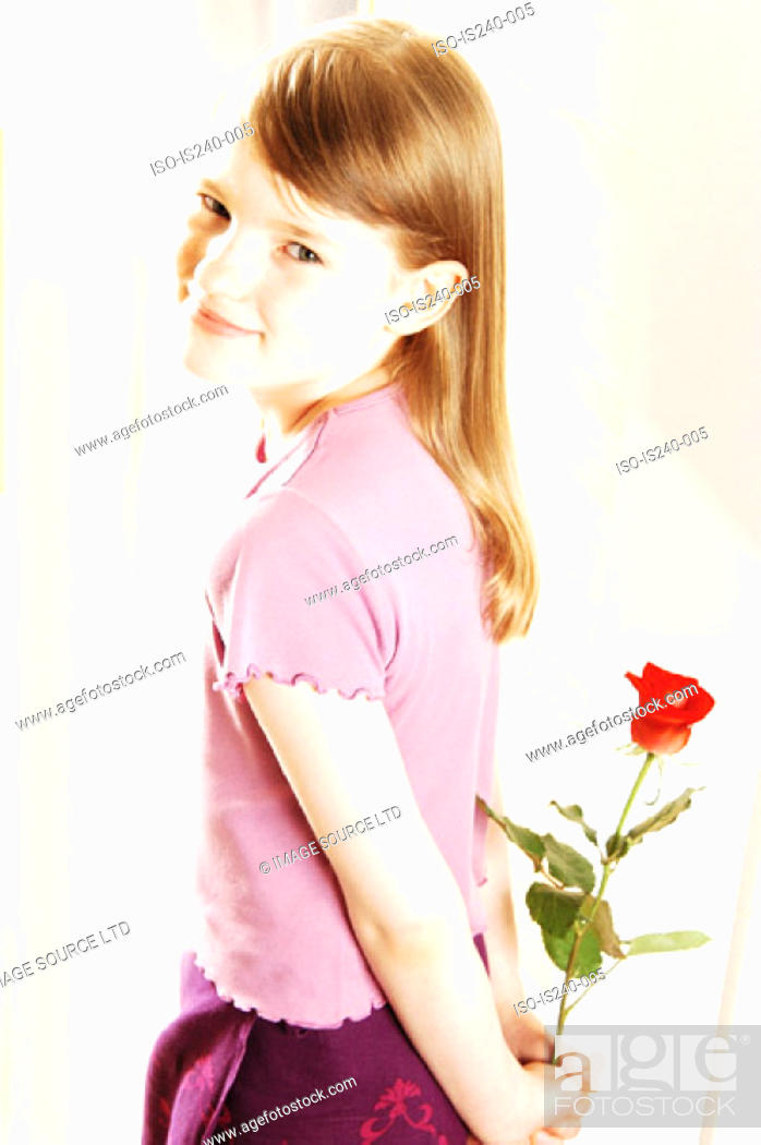 Stock Photo: Smiling girl holding red rose.