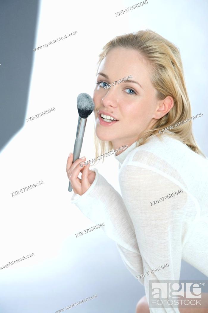 Stock Photo: young woman applying powder on face.