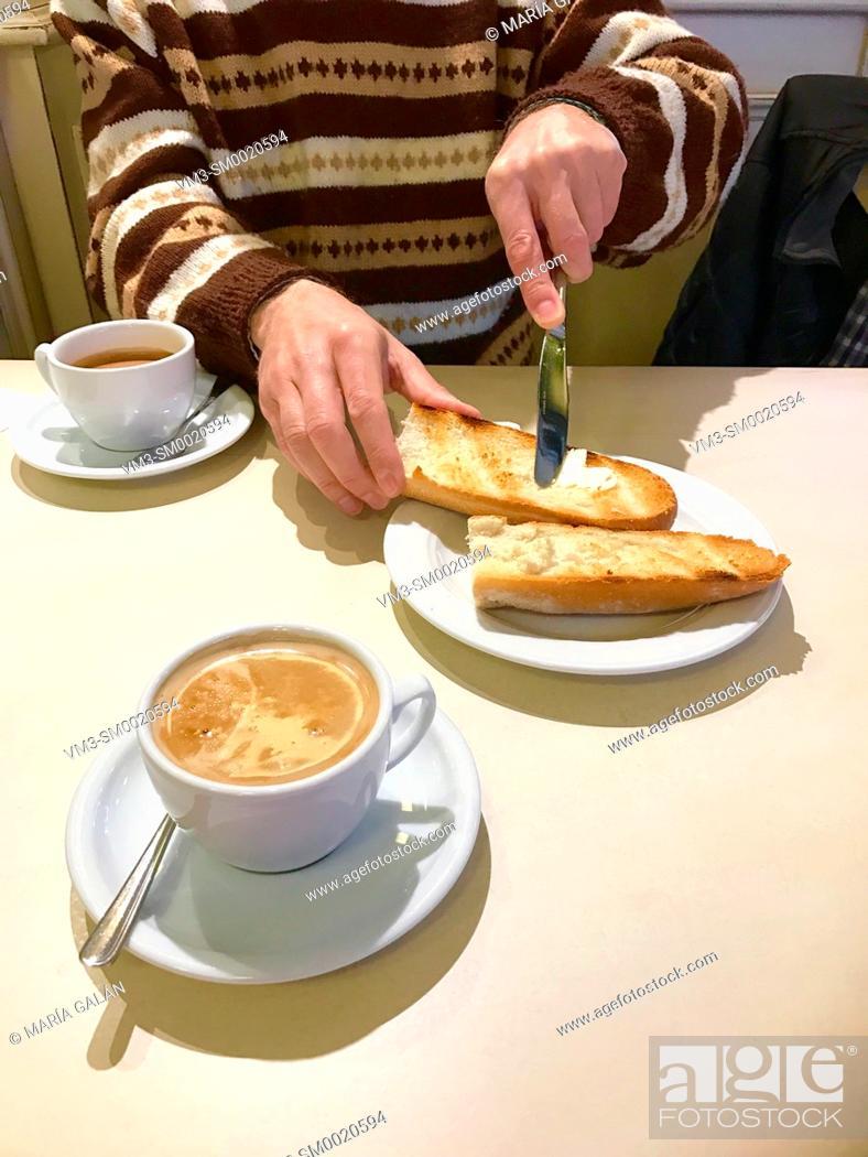 Stock Photo: Man having breakfast, spreading butter on toast.
