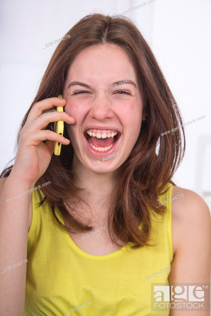 Stock Photo: Teenage girl using a cellphone, and laughing.
