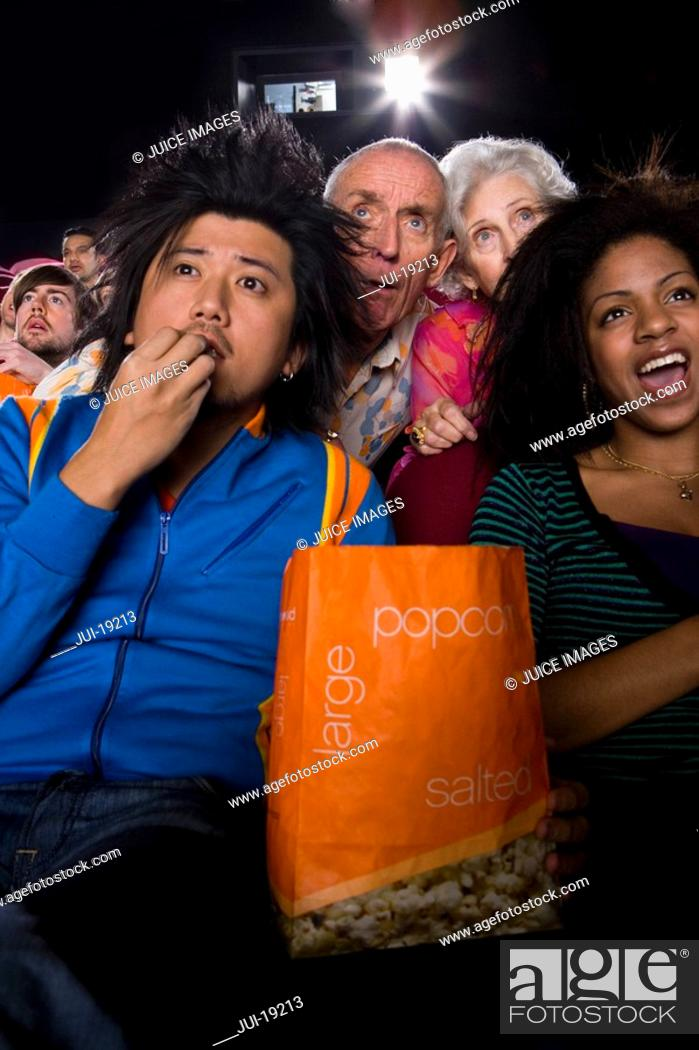 Stock Photo: Audience in cinema, man with popcorn, close-up, low angle view.