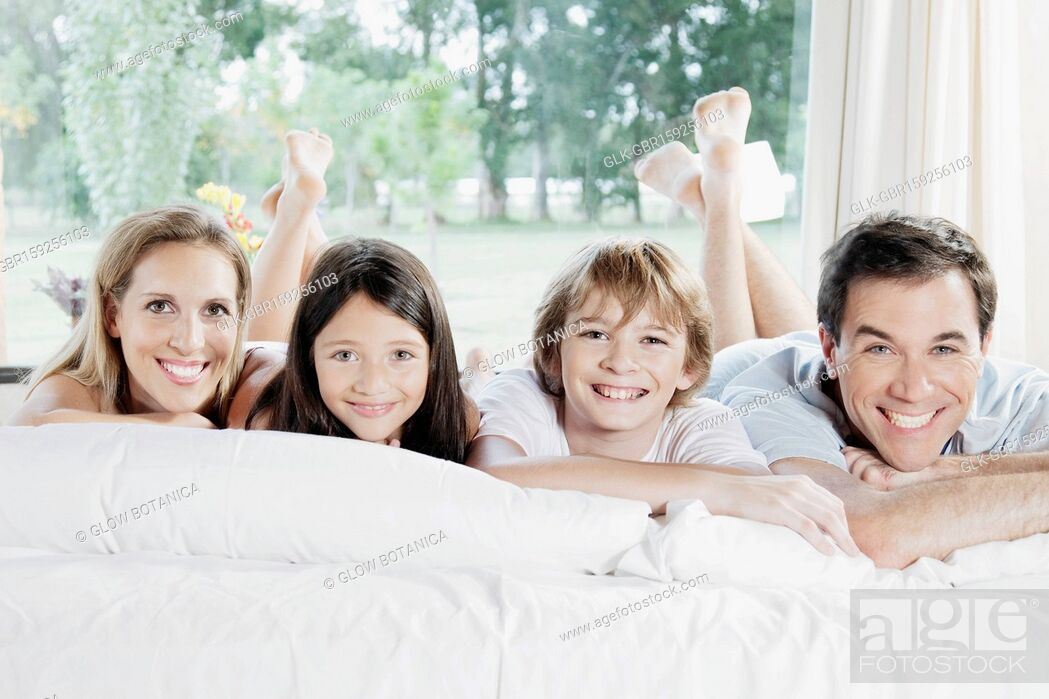 Stock Photo: Family lying on the bed and smiling.