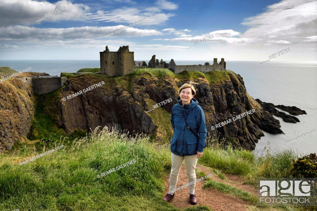 Stock Photo: Scottish female tourist visitor at top of cliff above Old Hall Bay with Donnottar Castle ruins on the North Sea Scotland UK.