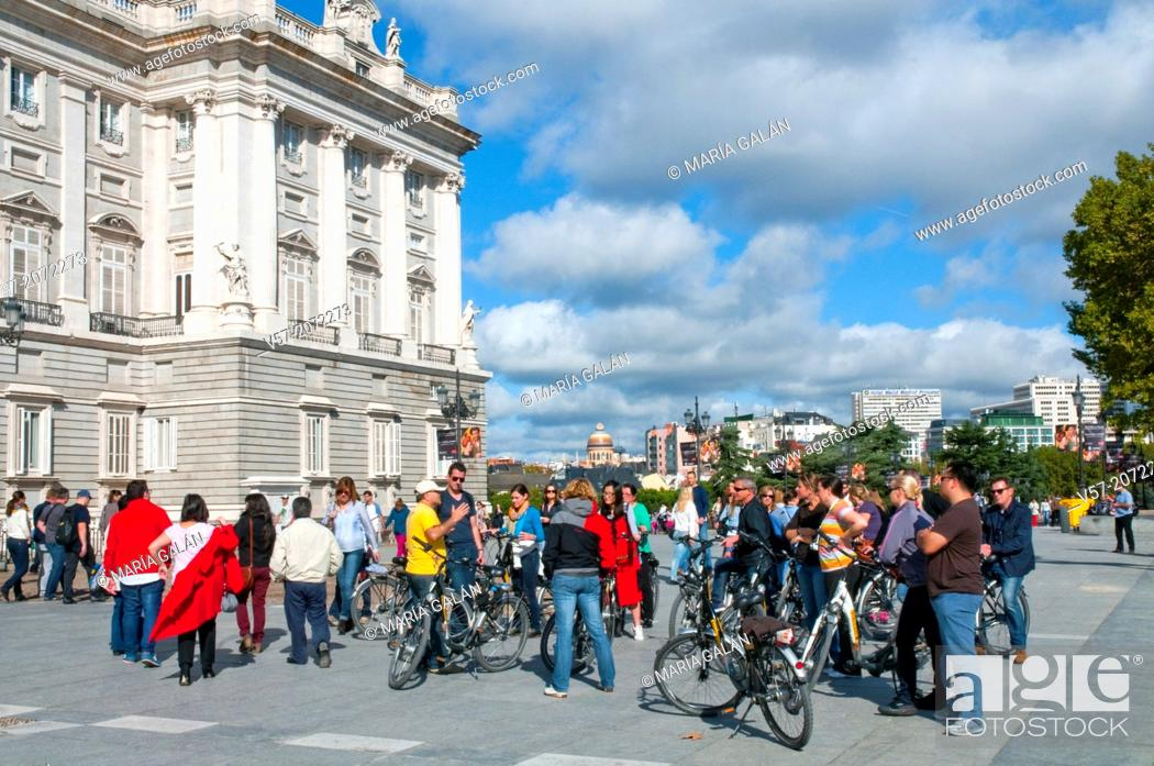 Stock Photo: Group of tourists with bicycles next to the Royal Palace. Bailen street, Madrid, Spain.