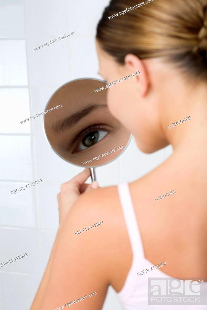 Stock Photo: Woman looking in mirror.