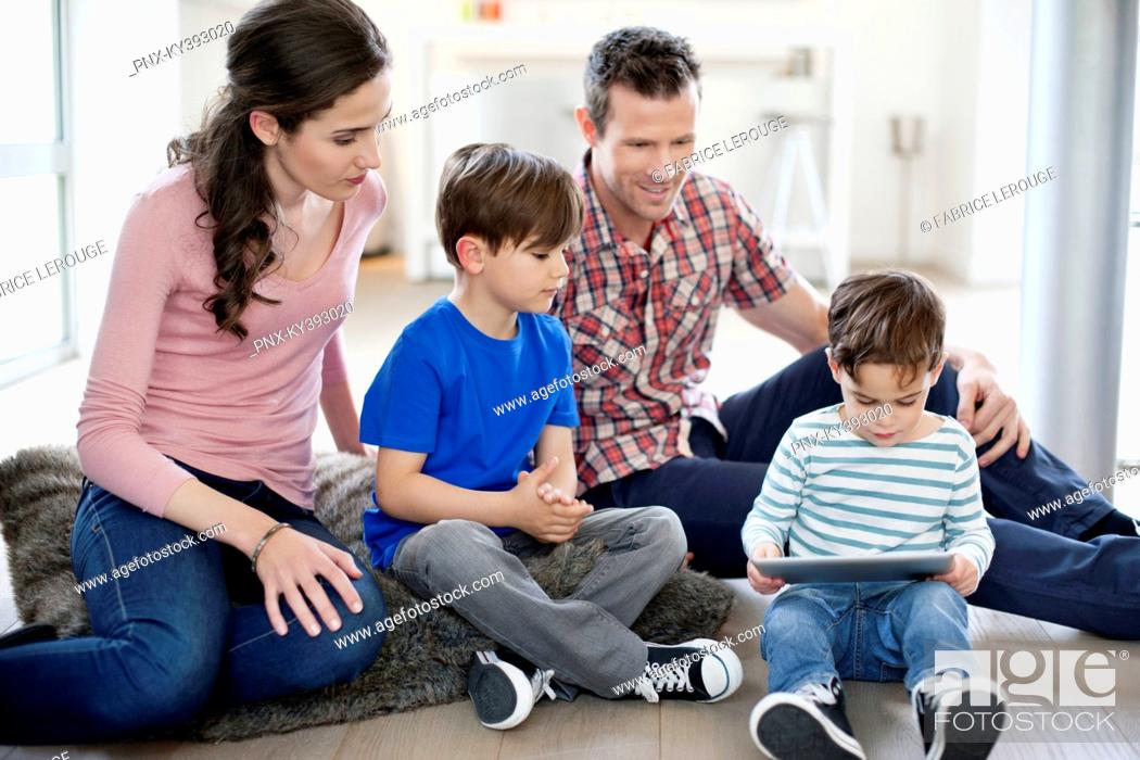 Stock Photo: Parents looking at their children using a digital tablet.