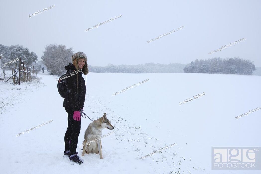 Imagen: Caucasian young woman with a wolf dog in snow landscape outdoor in winter time. Navarre, Spain, Europe.