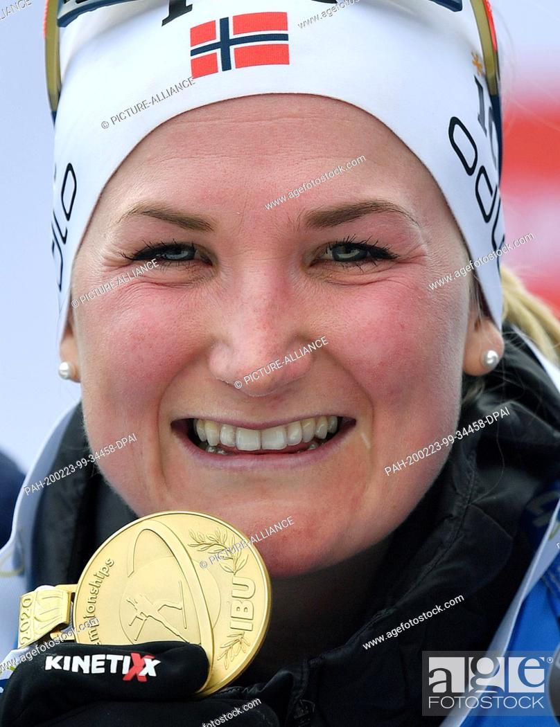 Stock Photo: 23 February 2020, Italy, Antholz: Biathlon: World Championship, mass start 12.5 km, women. Marte Olsbu Roeiseland from Norway shows her gold medal after winning.