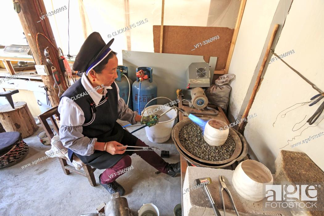 Stock Photo: Bai woman making a silver pot. Heqing is famous for the production of Silverware- Yunnan, China.