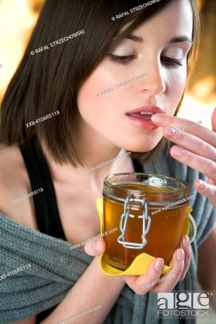 Stock Photo: young woman putting honey into lips.