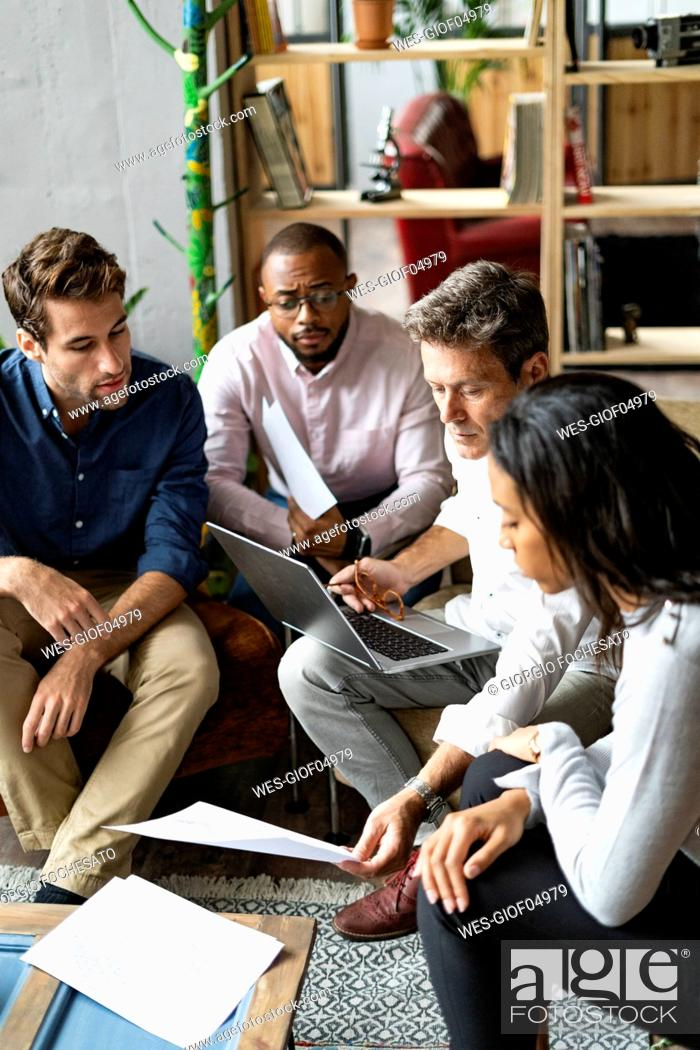 Stock Photo: Business team using laptop and discussing documents in loft office.