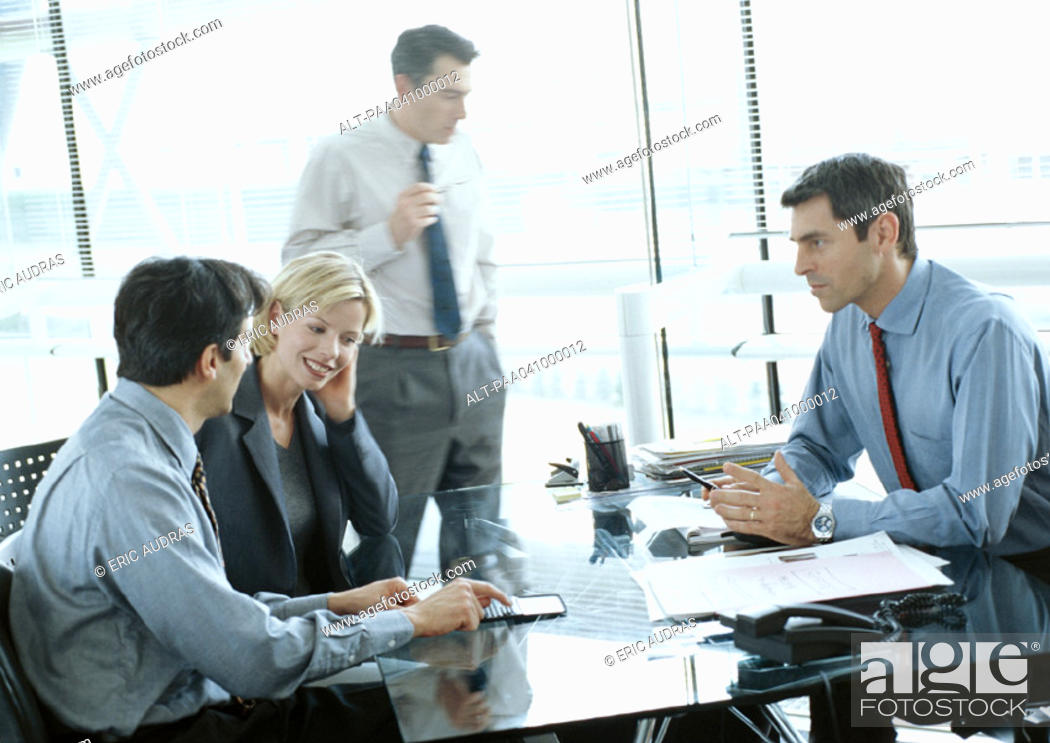 Stock Photo: Four business people in conference room, blurred.