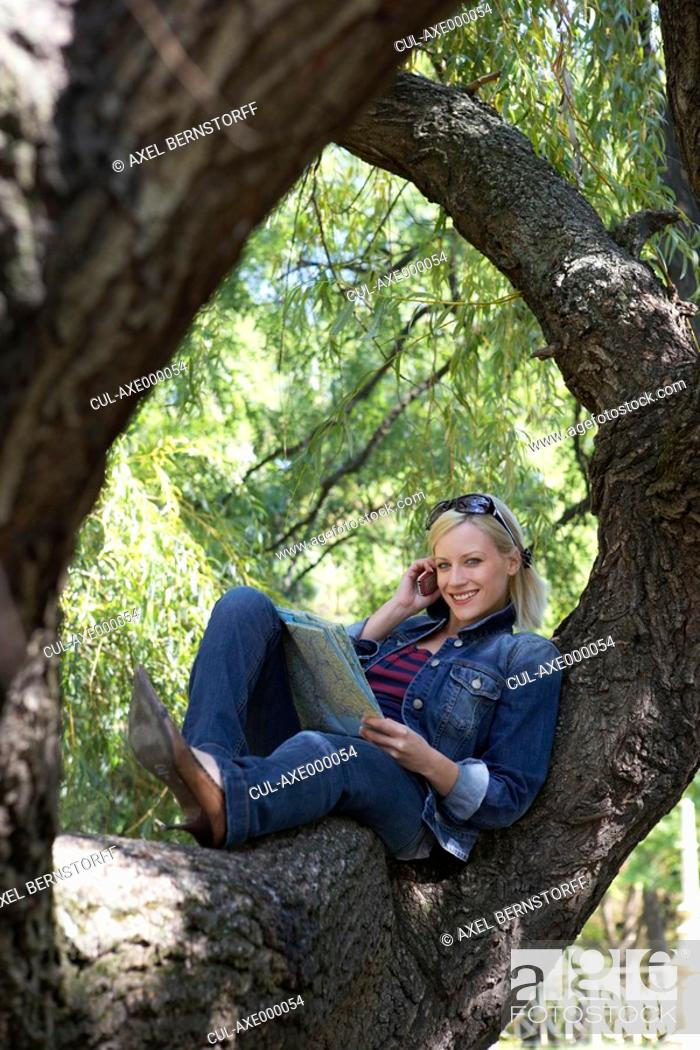Stock Photo: Woman sitting in a tree on cellular phone smiling.