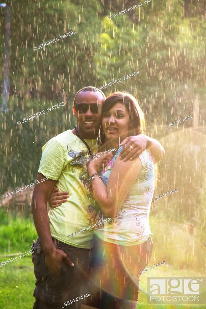 Stock Photo: A happy, young, african-american couple playing in the rain.