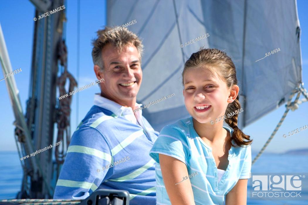 Stock Photo: Father and daughter 8-10 sitting on deck of sailing boat, smiling, portrait.