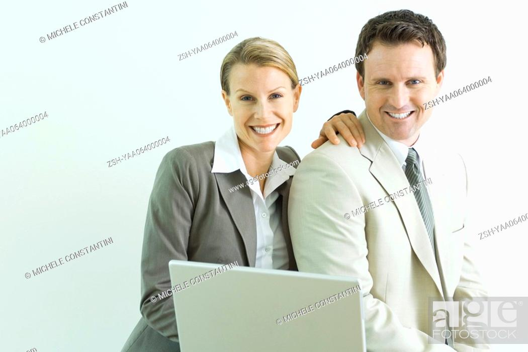 Stock Photo: Male and female business associates using laptop computer together, both smiling at camera.