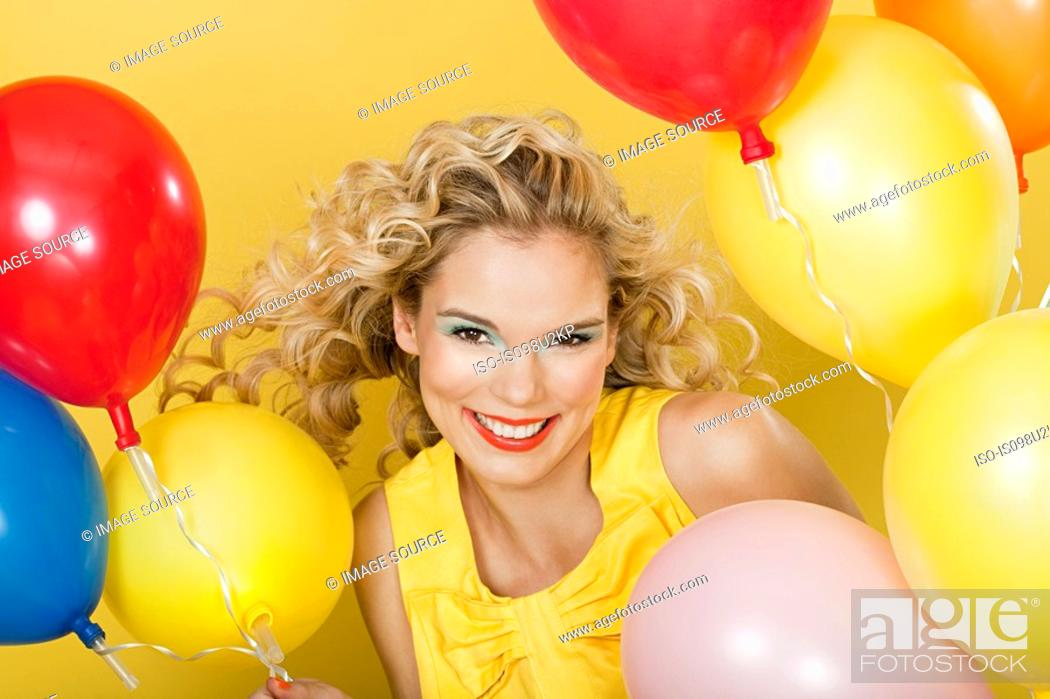 Stock Photo: Young blonde woman with balloons against yellow background.