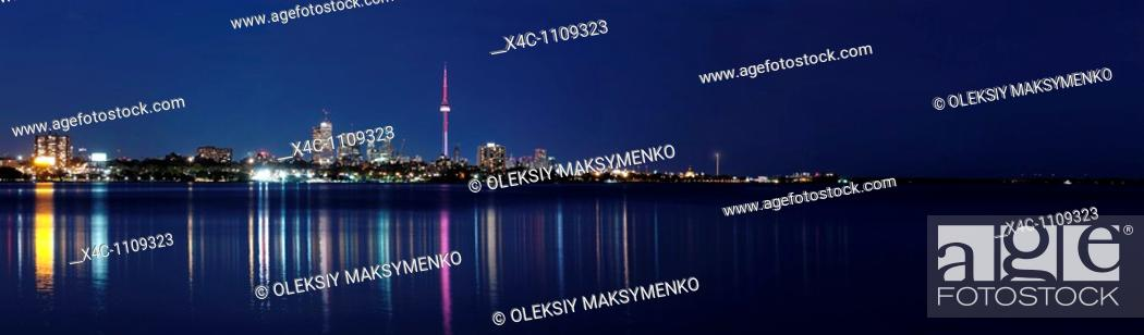 Stock Photo: Beautiful atmospheric panoramic view of a Toronto cityscape reflecting in lake Ontario water at night Toronto Ontario Canada.