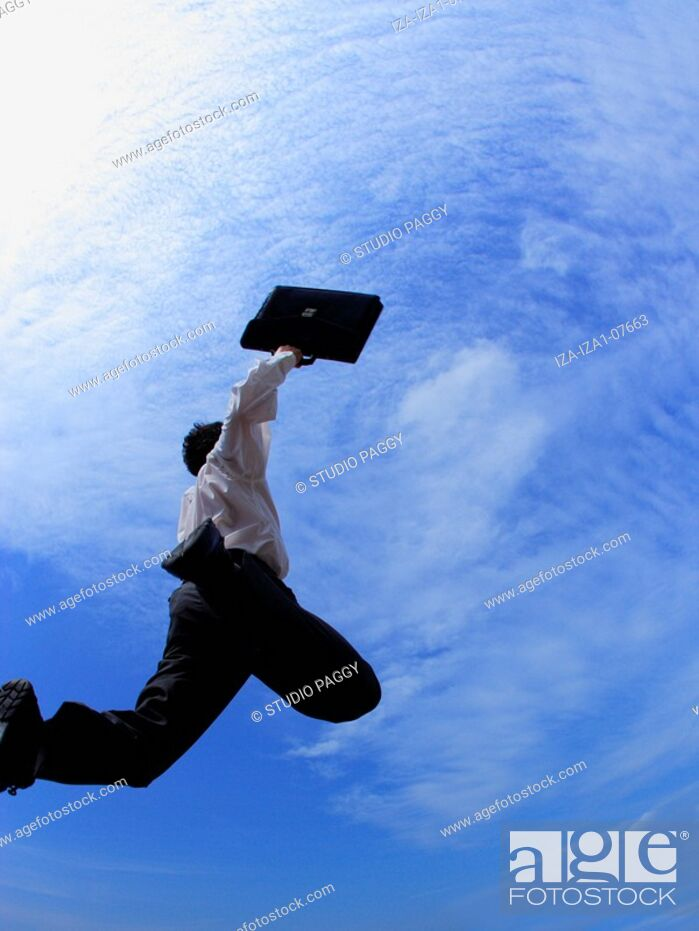 Imagen: Low angle view of a businessman jumping in mid-air.