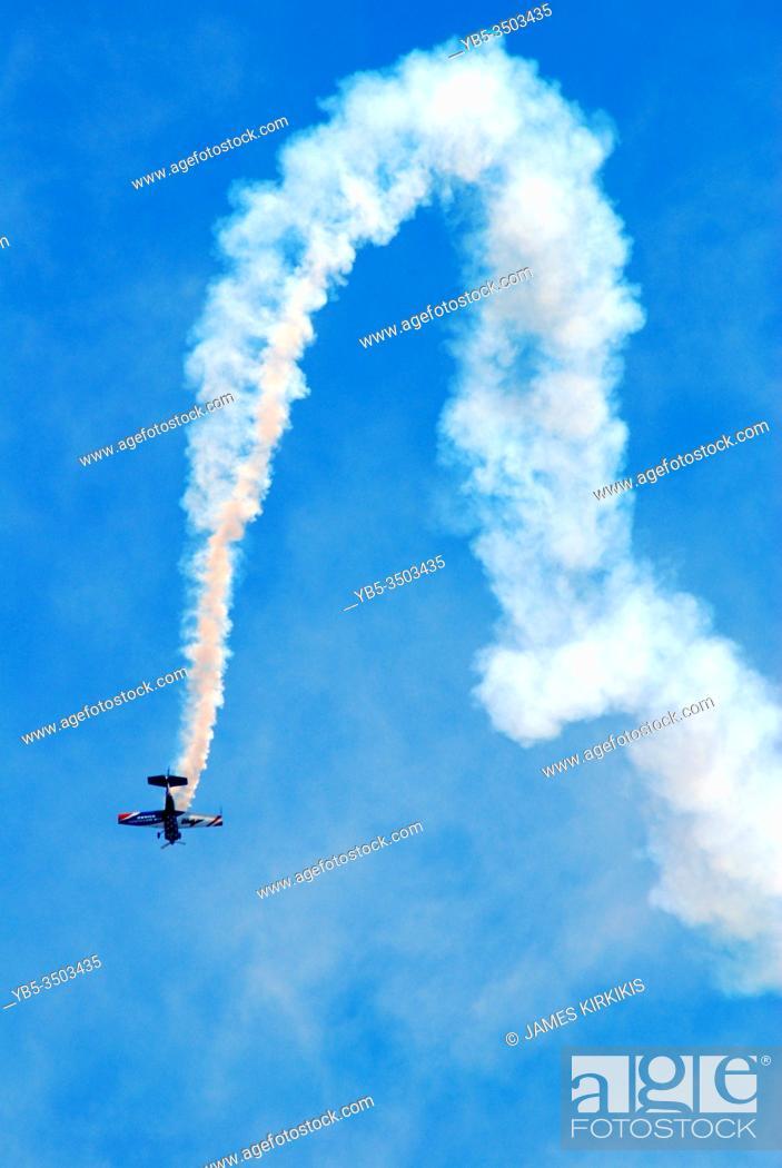 Stock Photo: A stunt pilot makes an arching descent at an air show.