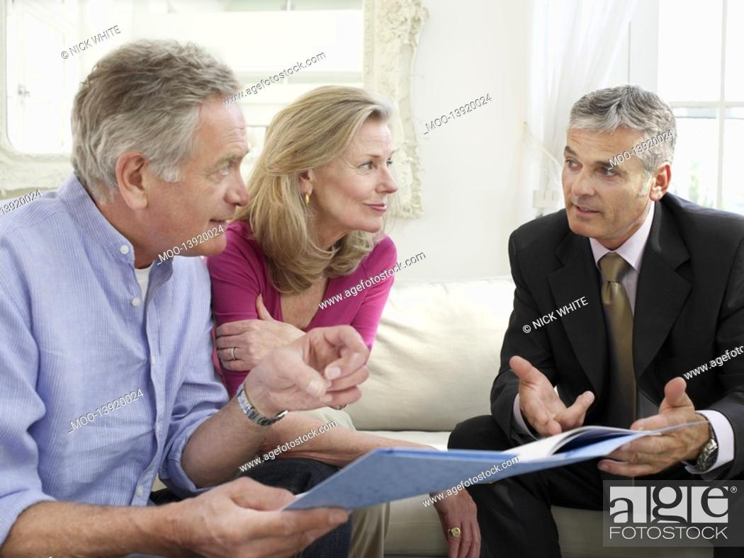 Stock Photo: Senior couple sitting on sofa with financial advisor.