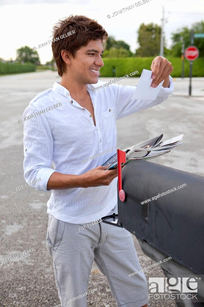 Stock Photo: A smiling man getting his mail from a mailbox.