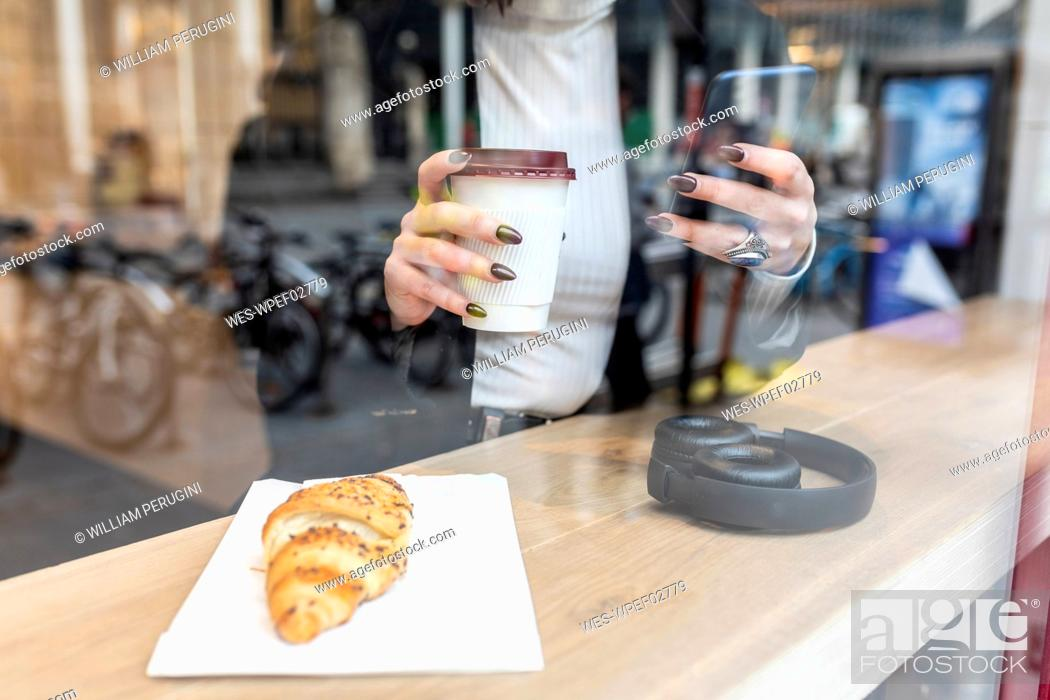 Stock Photo: Close-up of businesswoman having a coffee break and using mobile phone at a cafe in the city.