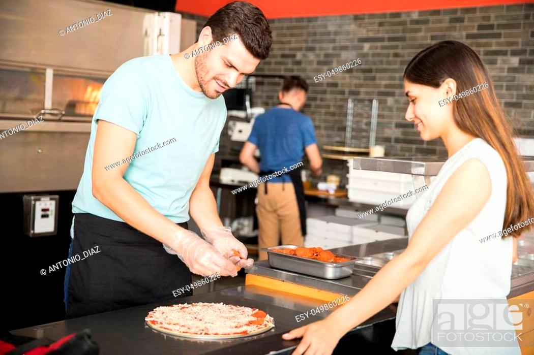 Imagen: Chef wearing gloves preparing pizza adding pepperoni while customer looking at pizza in pizzeria.