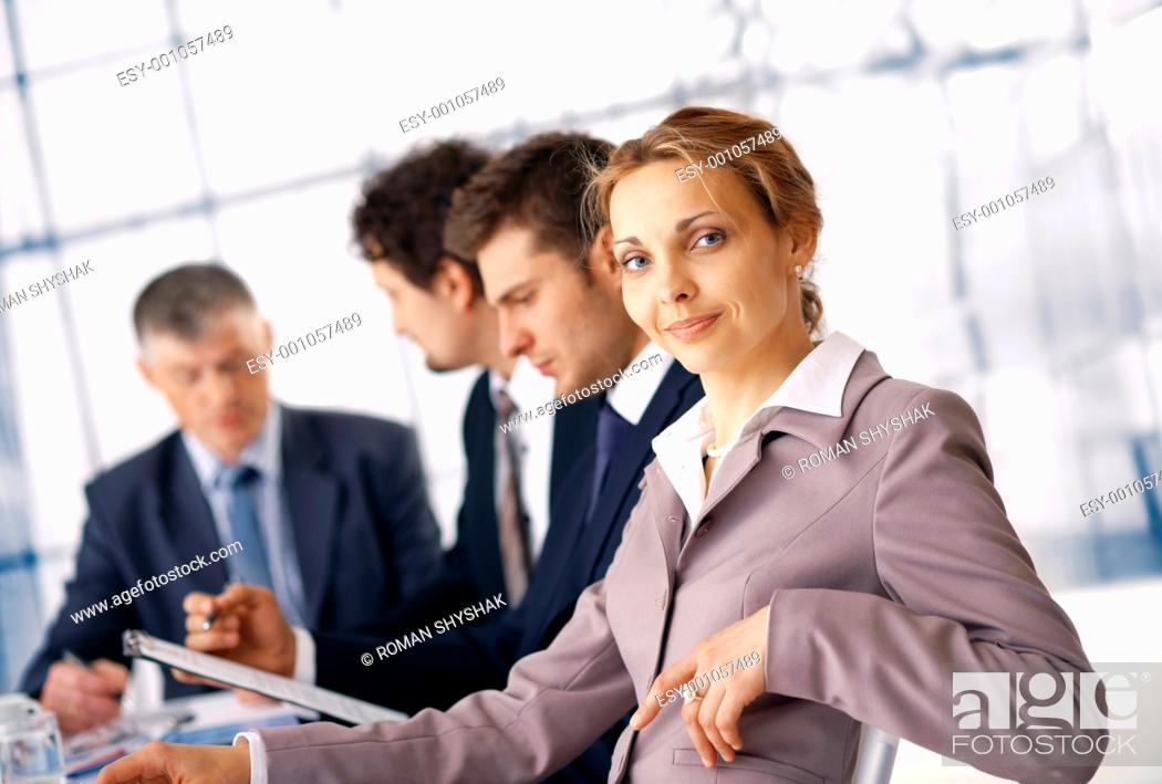 Stock Photo: Business woman sitting at the business meeting with her colleagues at the background.
