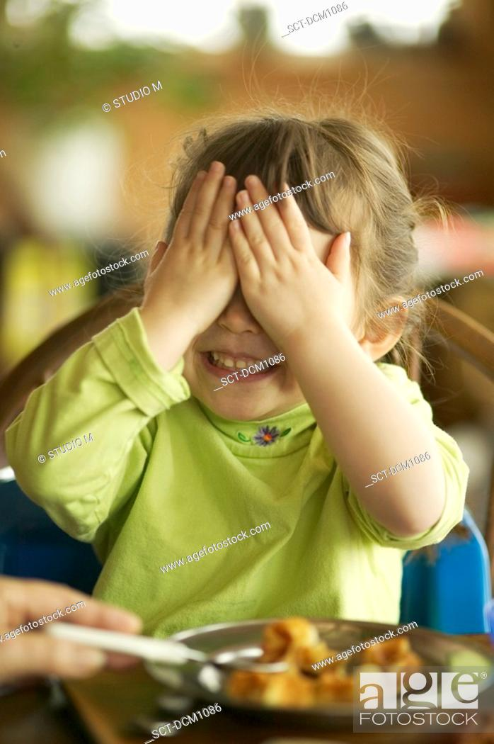 Stock Photo: Close-up of a child covering her eyes as she is about to be spoon fed.