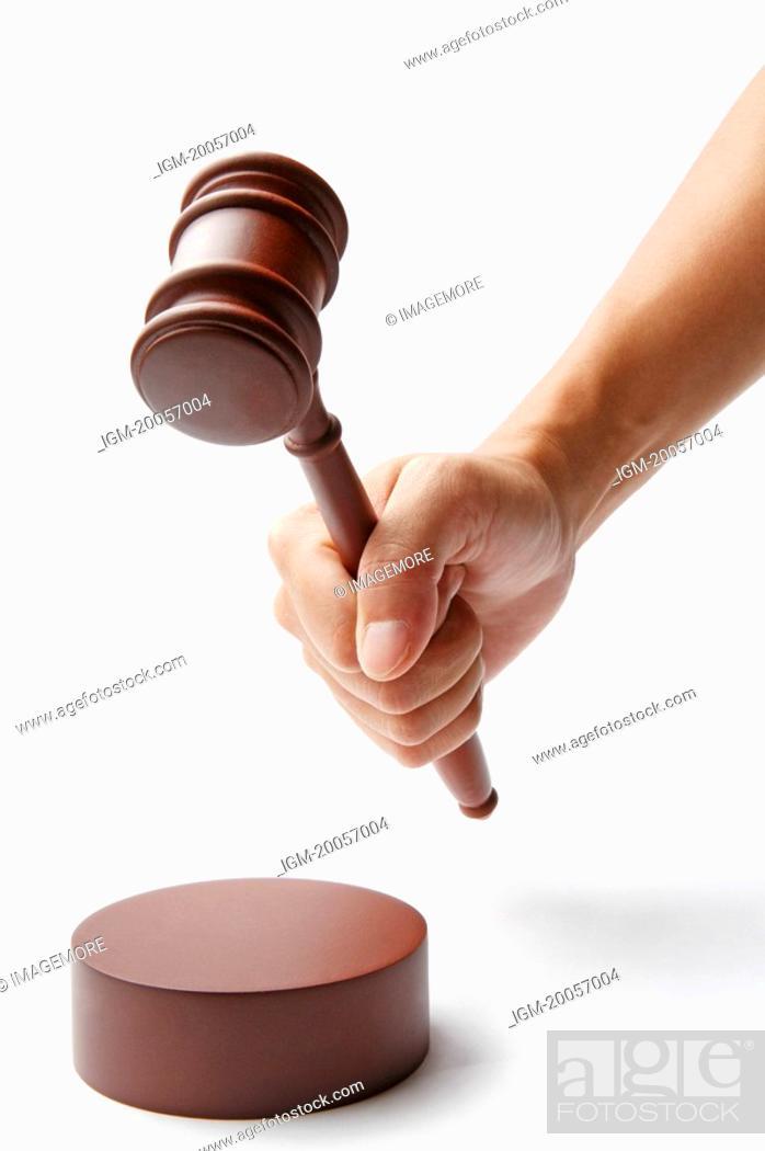 Stock Photo: Human hand holding a gavel.