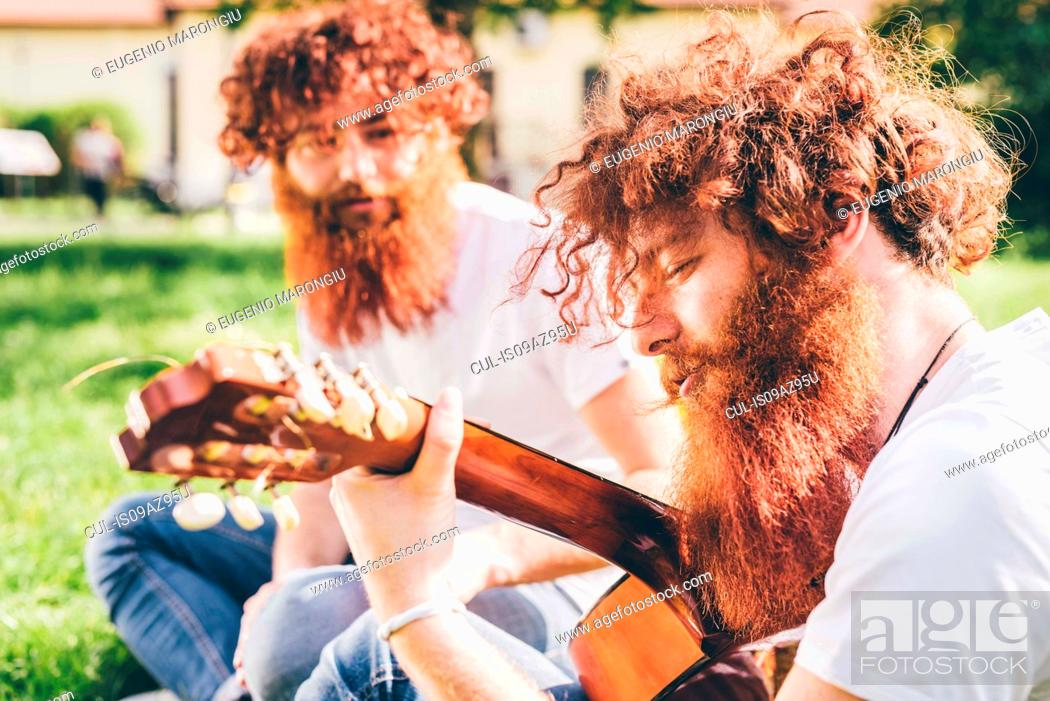 Stock Photo: Young male hipster twins with red beards sitting in park playing guitar.