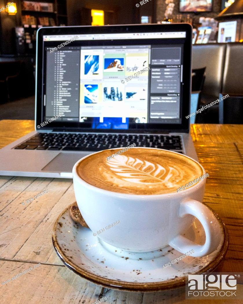 Imagen: Coffee with froth art and laptop on table.