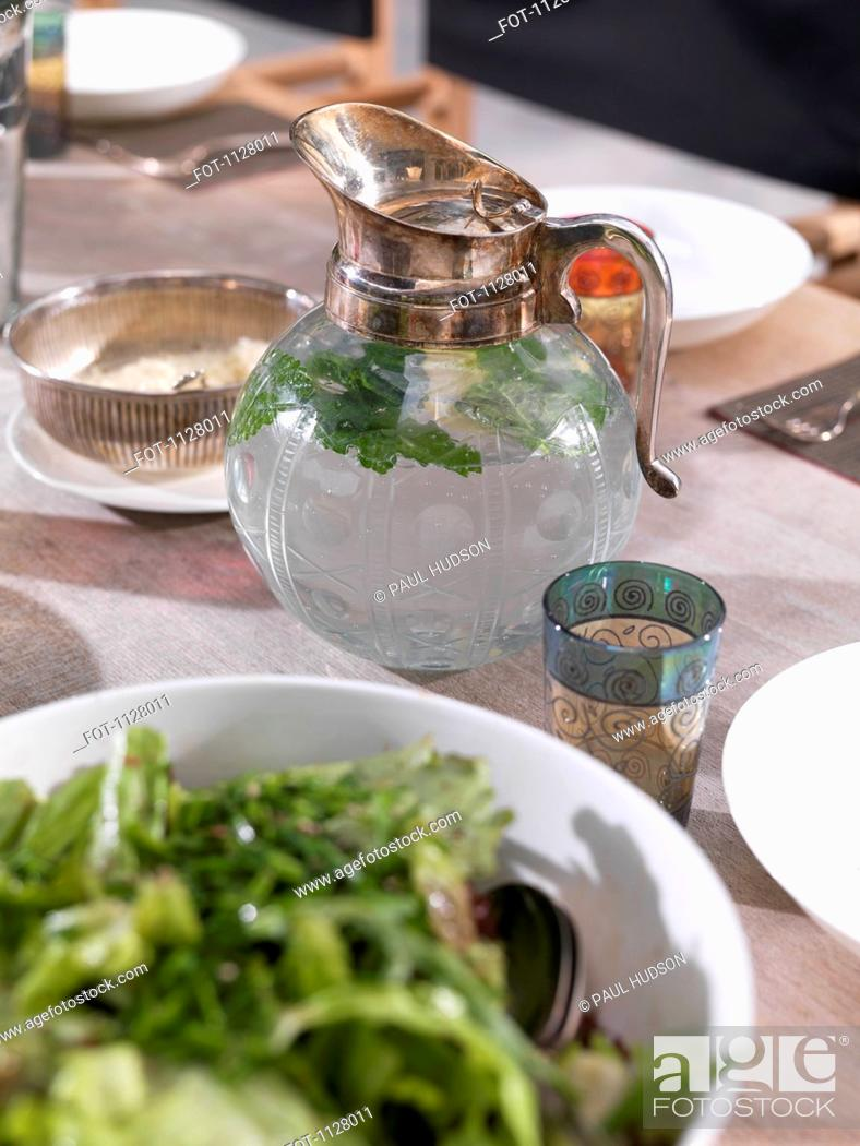 Stock Photo: A jug of water and a glass on a dining table.