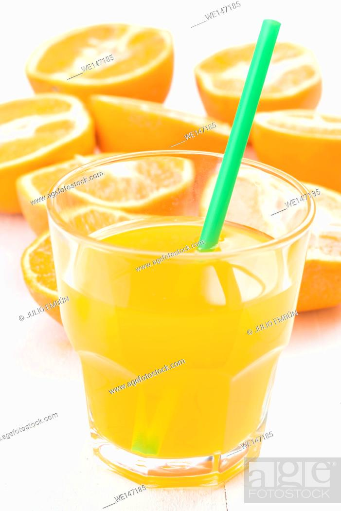 Photo de stock: glass of juice and cut oranges on white table.