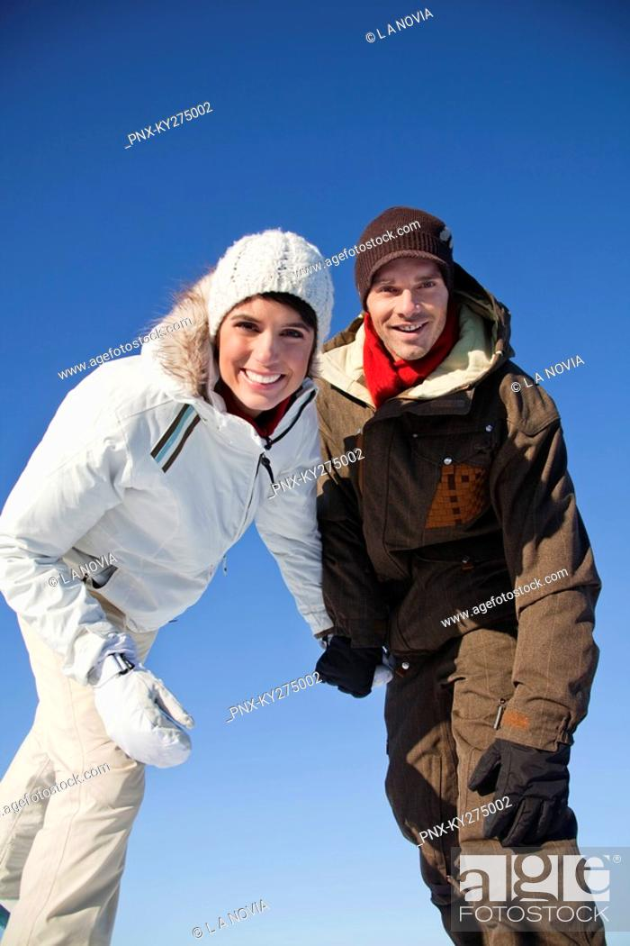 Stock Photo: Young couple wearing ski wear, smiling at camera.