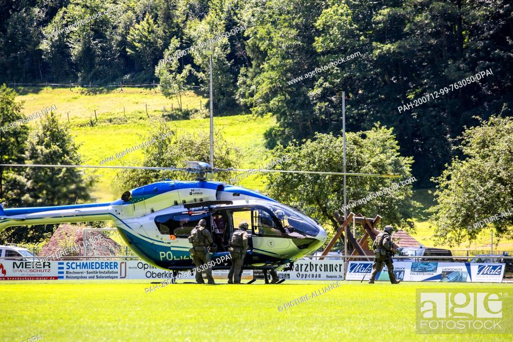 Stock Photo: 12 July 2020, Baden-Wuerttemberg, Oppenau: Police officers of a SEK leave a helicopter that has just landed. A man armed with bows and arrows threatened.