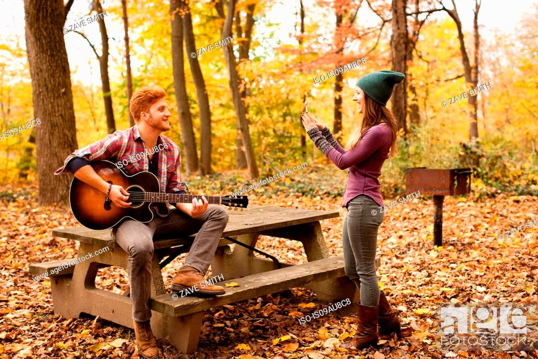 Imagen: Young woman photographing guitar playing boyfriend in autumn forest.