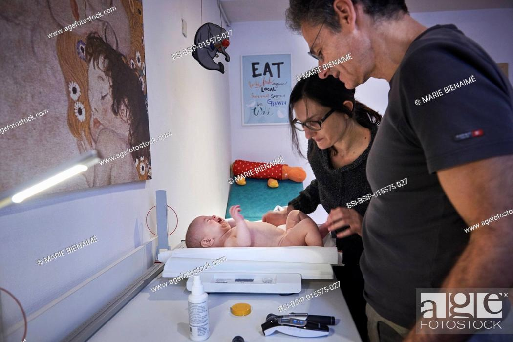 Stock Photo: Reportage on a pediatrician who specializes in attachment theory in Lyon, France. A consultation at 4 months old. Being weighed.