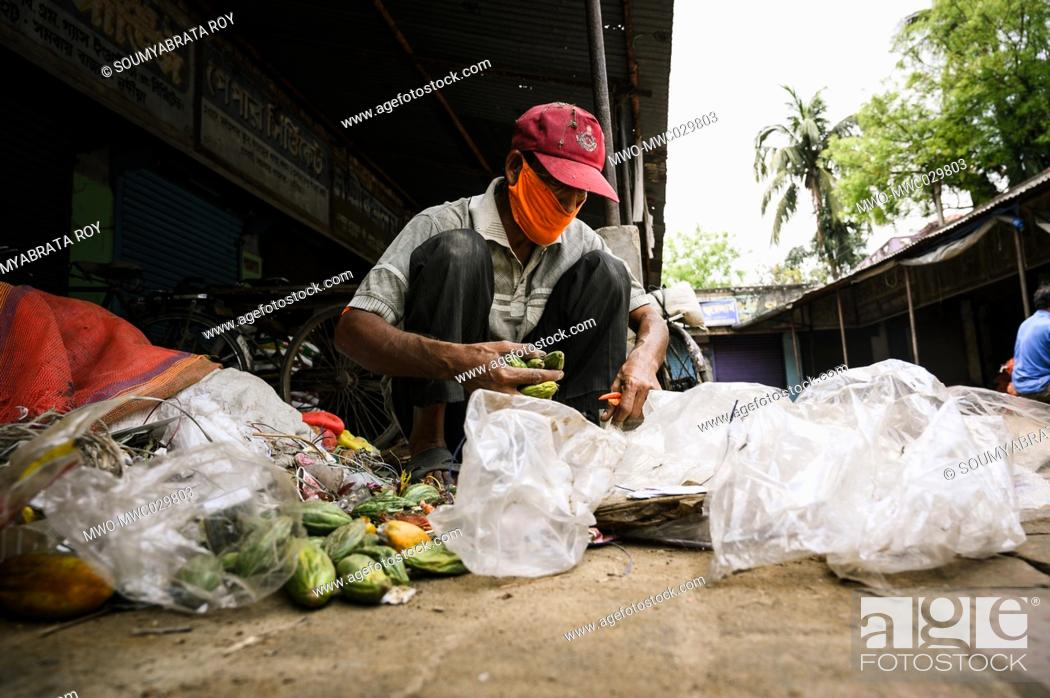 Imagen: After sweeping the market the whole day a worker is collecting dry vegetables from the trash without gloves at Tehatta. The West Bengal government has.