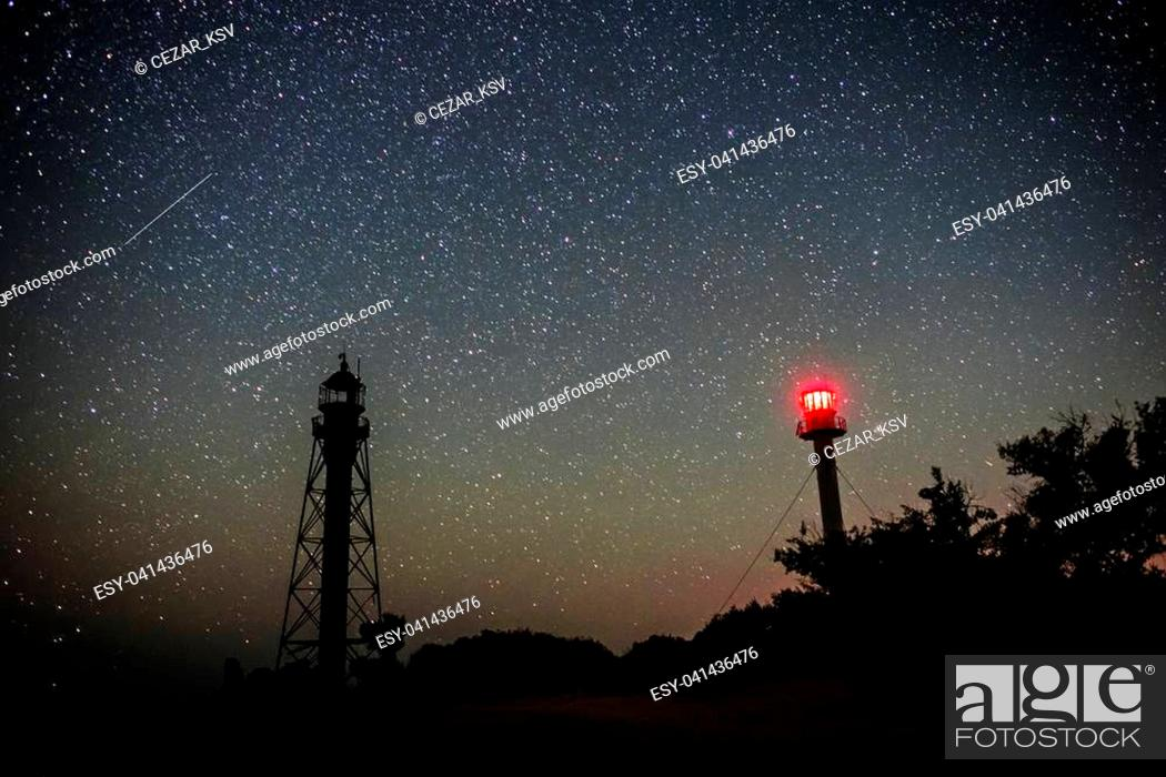 Stock Photo: Silhouettes of the twoLighthouse sandy beach and ocean against the background of the starry sky.