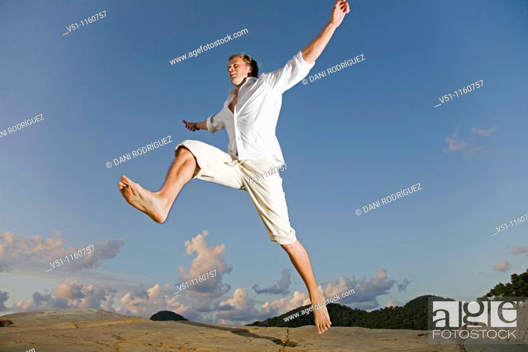 Stock Photo: Man jumping in a cliff in Ibiza.