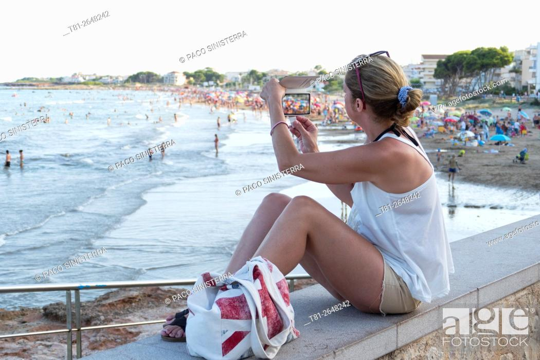 Stock Photo: woman looking at cell phone on vacation. Alcocebre. Spain.