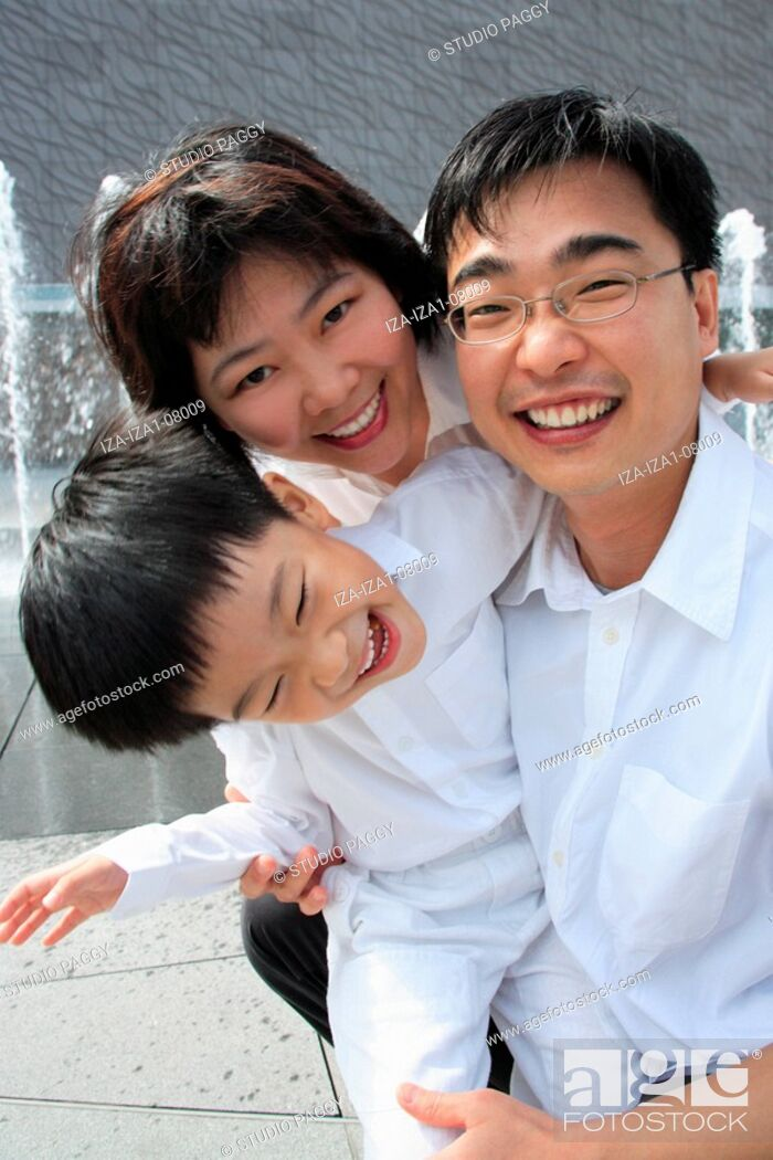 Imagen: Mid adult couple smiling with their son in a park.