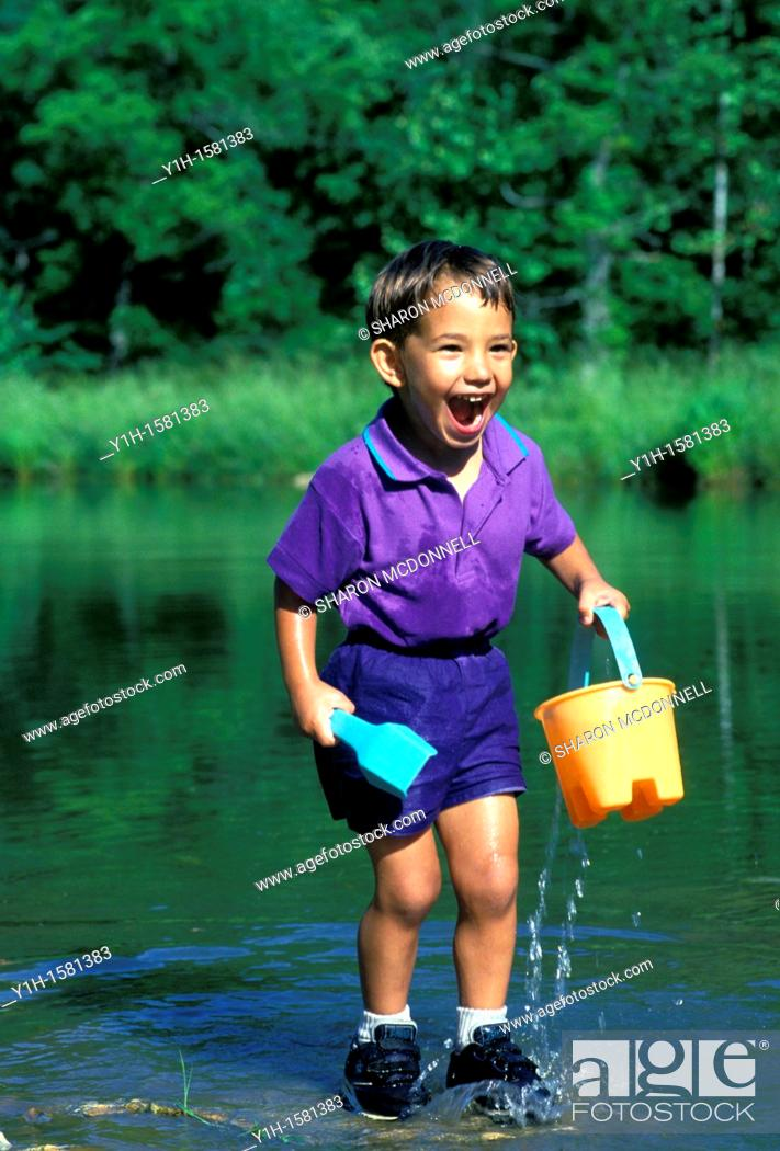 Stock Photo: Afghan-American boy thrilled with water play in pond, summer, Midwest USA.