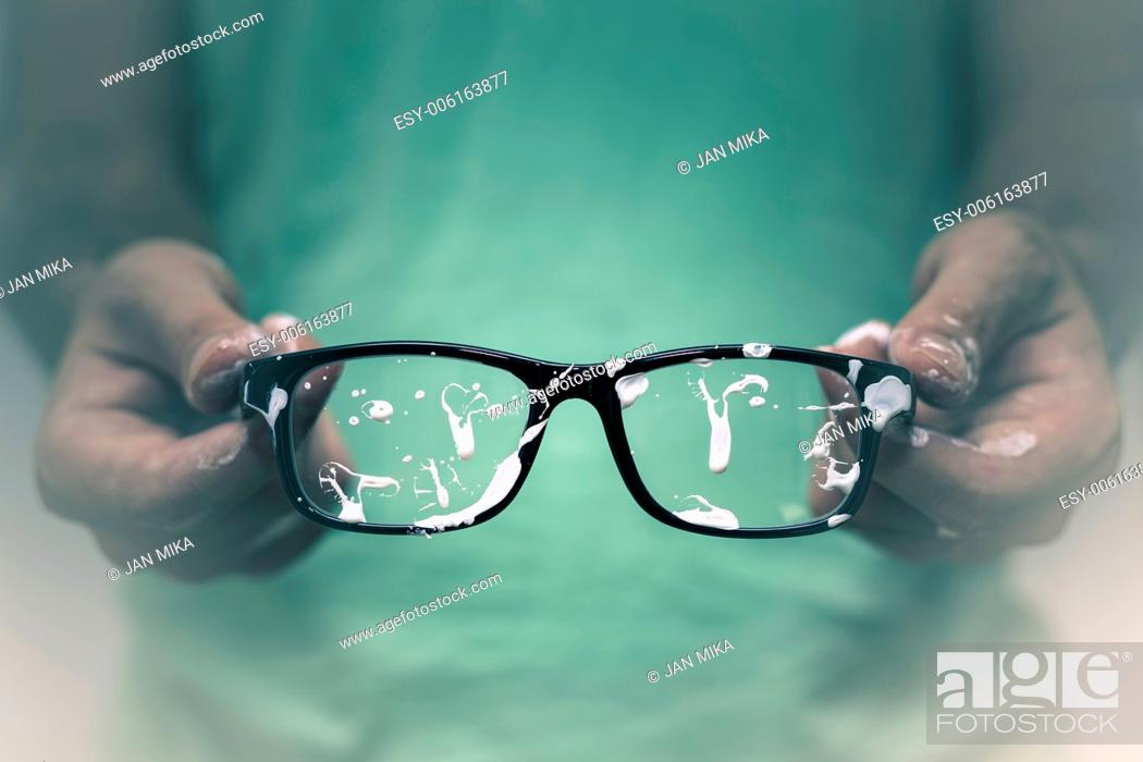 Imagen: Creative vision concept. Closeup of creative man showing his stained eyeglasses.