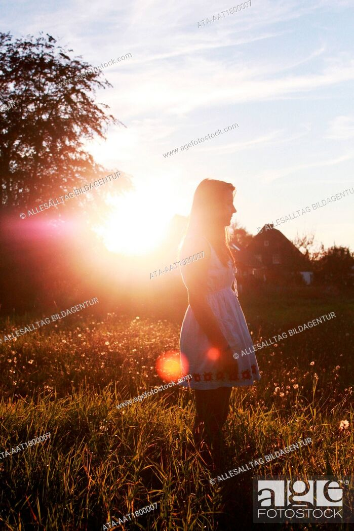 Stock Photo: Young girl watching the sundown.