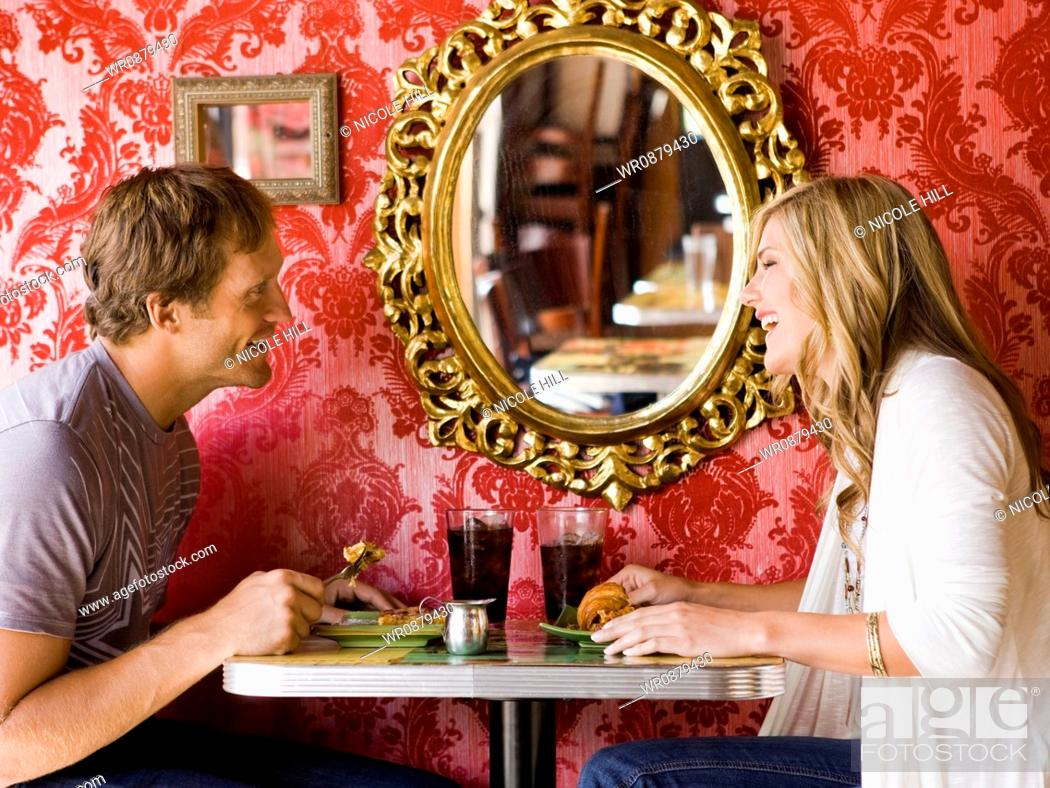 Stock Photo: young couple eating together at a diner.
